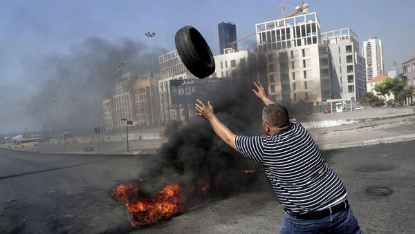 Демонстрант сжигает шины в Бейруте - Sputnik Азербайджан