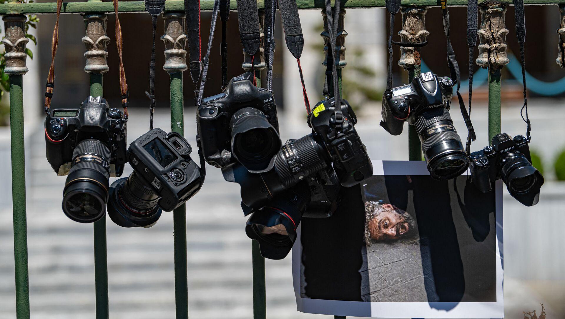 Фотоаппараты висят на решетке, фото из архива - Sputnik Azərbaycan, 1920, 19.08.2021