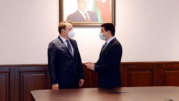 Встреча комиссара Европейского Союза (ЕС) по вопросам соседства и расширения Оливера Вархели с помощником Президента АР Хикметом Гаджиевым - Sputnik Азербайджан