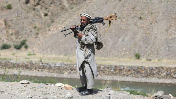 Вооруженный человек, выступающий против восстания талибов, стоит на контрольно-пропускном пункте в районе Горбанд, провинция Парван, Афганистан, 29 июня 2021 года. - Sputnik Azərbaycan