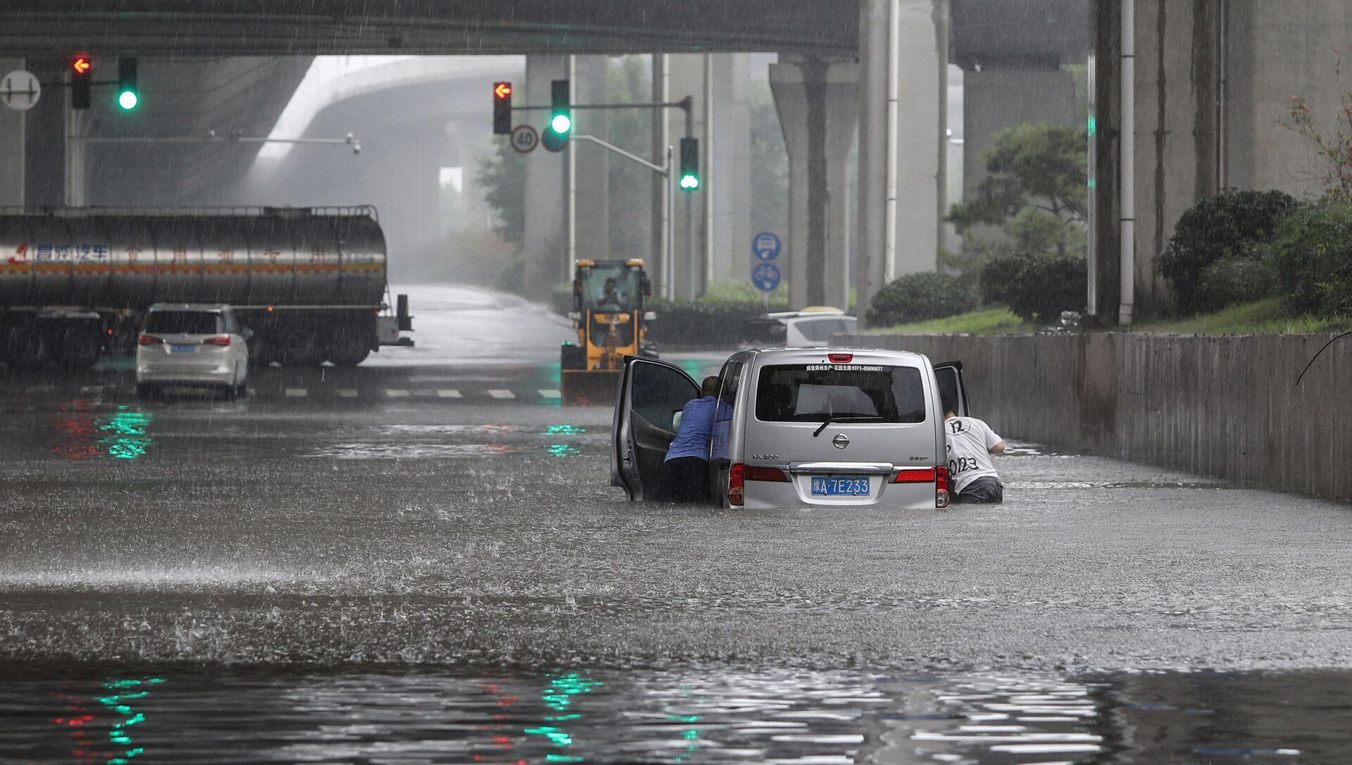 Люди толкают машину на затопленной улице в Чжэнчжоу, Китай - Sputnik Азербайджан, 1920, 23.07.2021