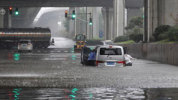 Люди толкают машину на затопленной улице в Чжэнчжоу, Китай - Sputnik Азербайджан