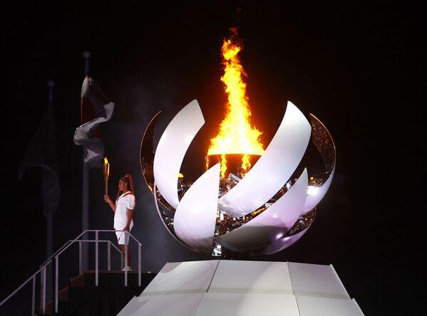 Наоми Осака из Японии держит олимпийский факел после зажжения олимпийского котла на церемонии открытия  - Sputnik Азербайджан