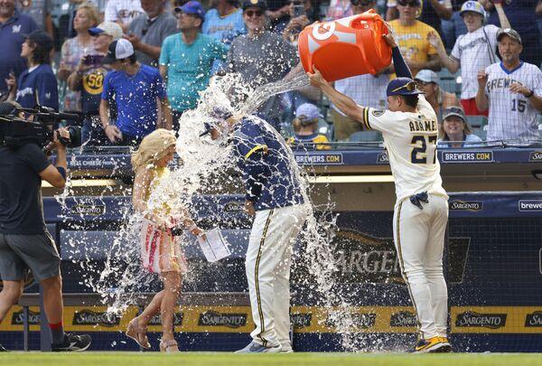 Вилли Адамес обливает водой своего товарища по команде Роуди Теллеса во время интервью после победы в бейсбольном матче, США - Sputnik Азербайджан