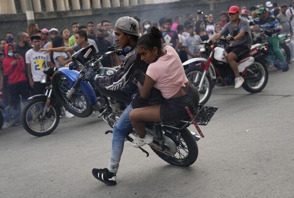 Мотоциклист проезжает с пассажиром во время выставки в районе Эль-Валле в Каракасе, Венесуэла  - Sputnik Азербайджан