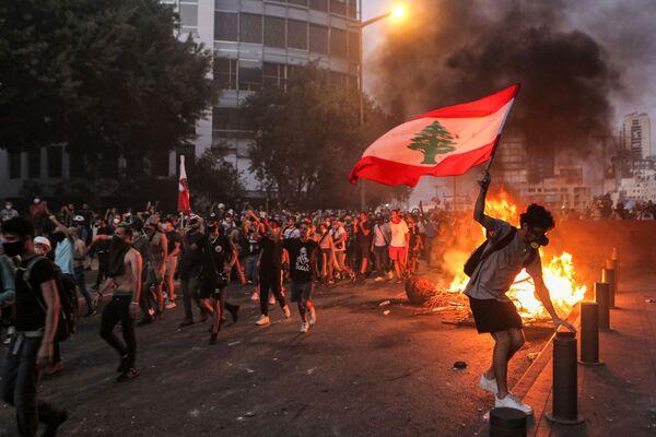 Протестующий с ливанским флагом во время столкновений в Бейруте - Sputnik Азербайджан