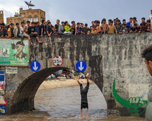 Молодые люди смотрят, как парень прыгает с моста через затопленный дренажный канал в старом городе столицы Йемена - Sputnik Азербайджан