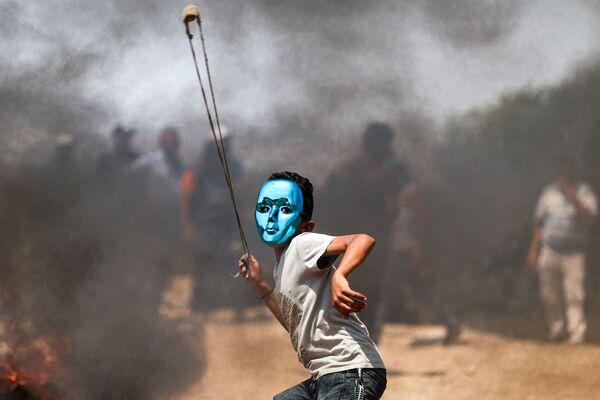 Палестинский ребенок в маске бросает камни во время столкновений с израильскими войсками в деревне Бейта на севере оккупированного Западного берега - Sputnik Азербайджан