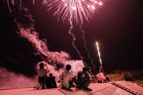 Люди запускают фейерверки на дамбе, реконструированной после цунами в 2011 году, в Минамисоме, префектура Фукусима, Япония - Sputnik Азербайджан