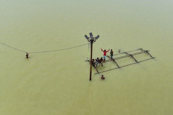 İnsanlar Hindistanda daşqınlar nəticəsində su basmış Daraqanc Qxatenin damında oturublar. - Sputnik Azərbaycan