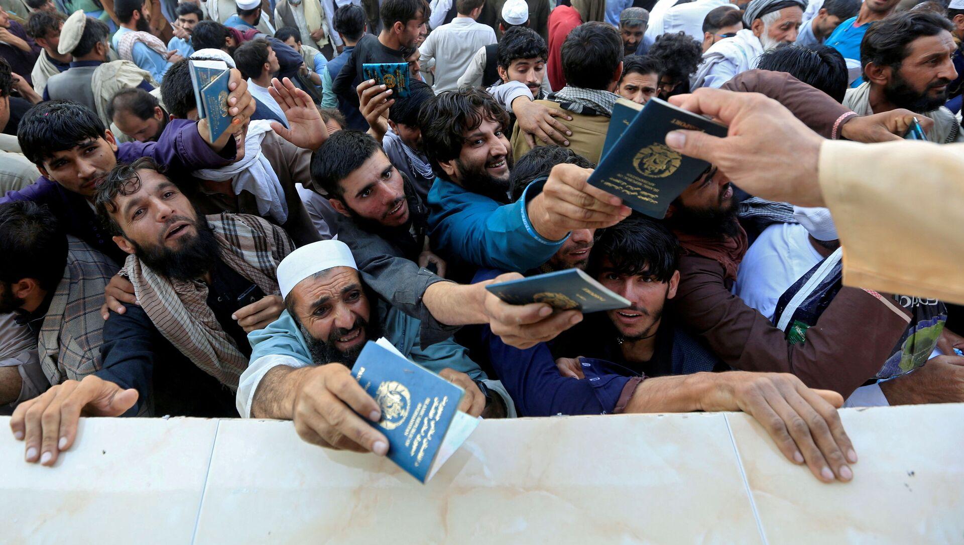 Афганские мужчины ждут, чтобы забрать жетоны, необходимые для подачи заявления на получение визы в Пакистан, в Джелалабаде, Афганистан - Sputnik Азербайджан, 1920, 17.09.2021