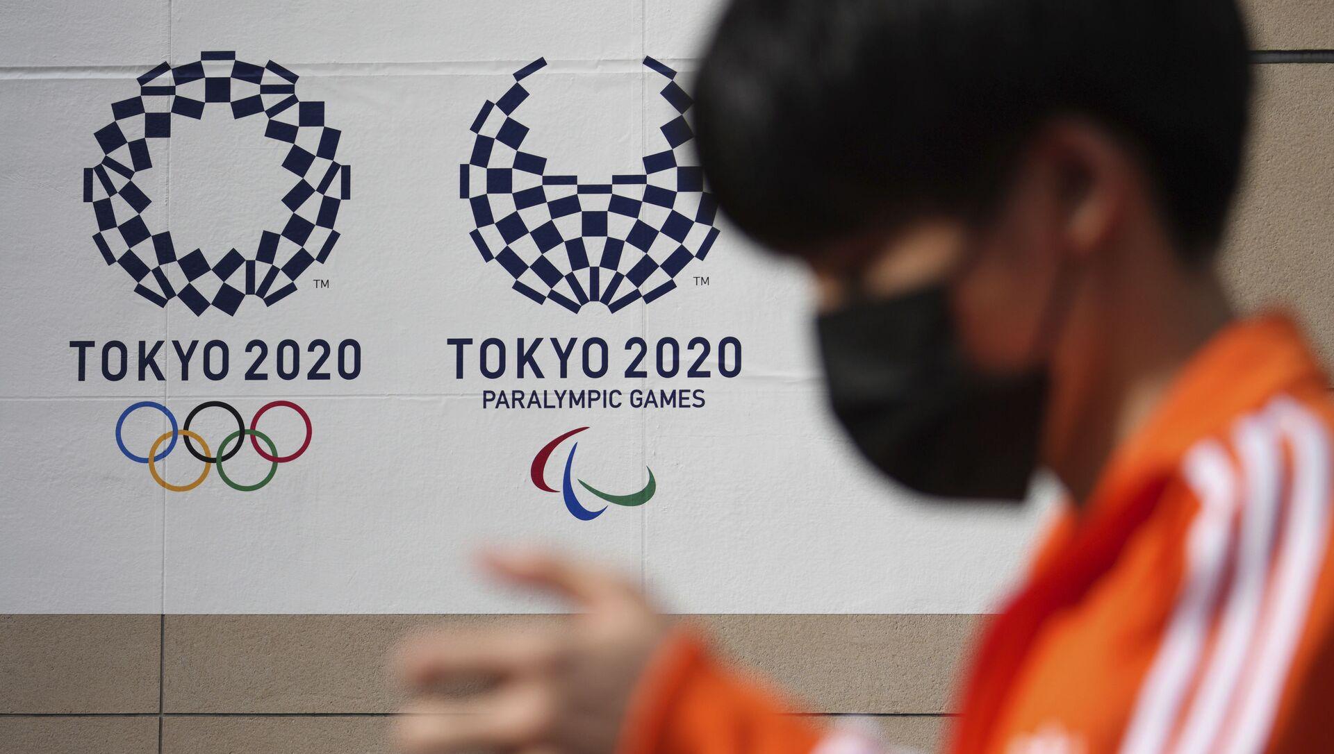 Мужчина в защитной маске, возле баннера Олимпийских и Паралимпийских игр в Токио-2020 - Sputnik Azərbaycan, 1920, 28.08.2021