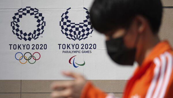 Мужчина в защитной маске, возле баннера Олимпийских и Паралимпийских игр в Токио-2020 - Sputnik Азербайджан