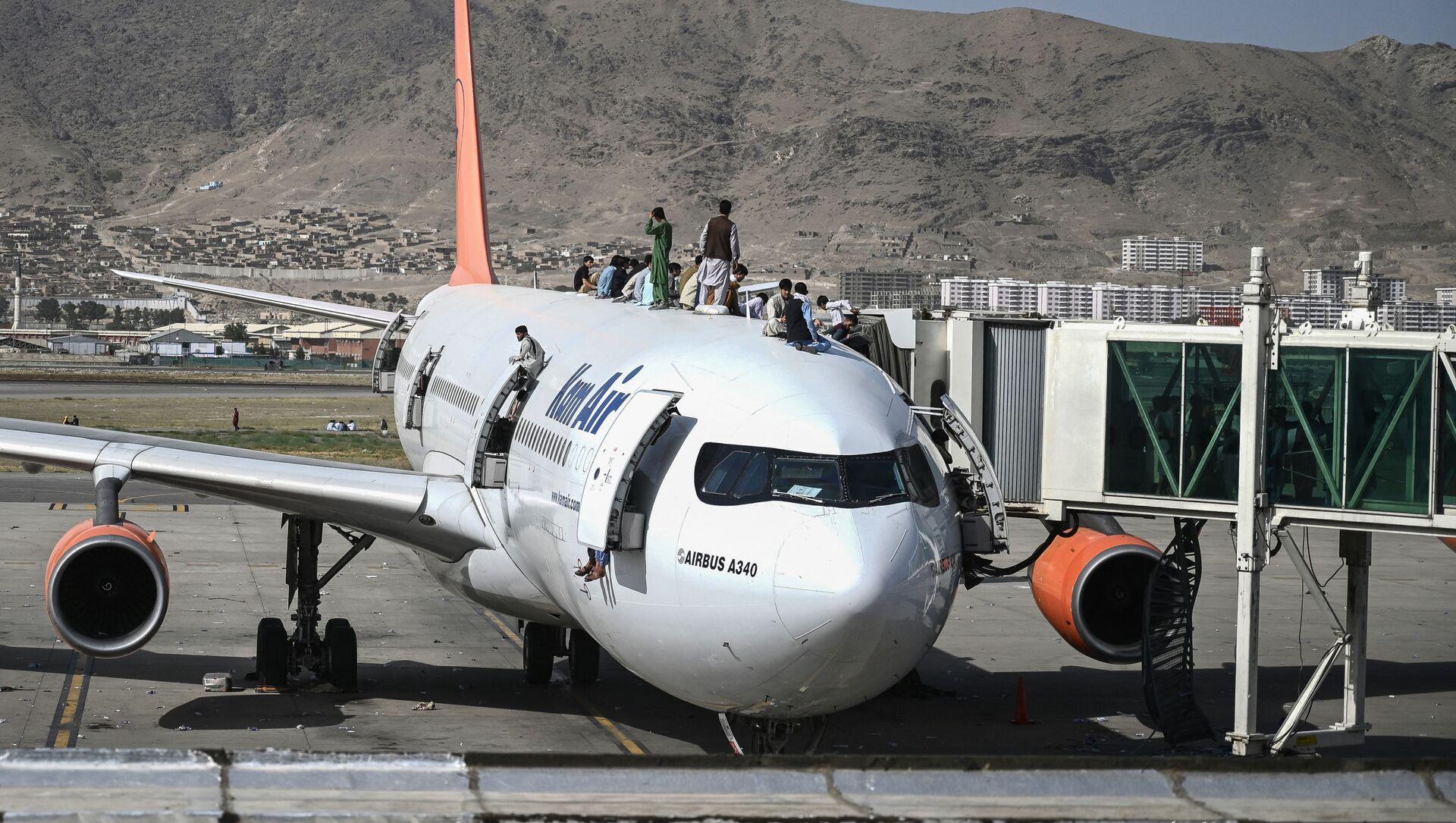 Афганцы забираются на самолет в кабульском аэропорту, 16 августа 2021 года. - Sputnik Азербайджан, 1920, 16.08.2021