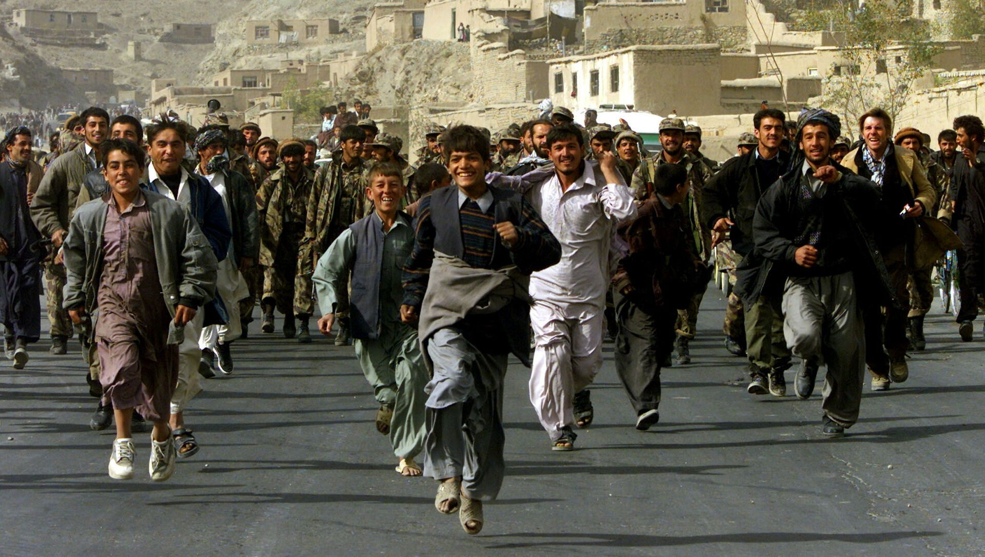 Жители Кабула сопровождают бойцов Северного Альянса, которые входят в Кабул, Афганистан, 13 ноября 2001 год. - Sputnik Азербайджан, 1920, 17.08.2021