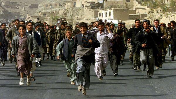 Жители Кабула сопровождают бойцов Северного Альянса, которые входят в Кабул, Афганистан, 13 ноября 2001 год. - Sputnik Azərbaycan