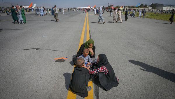 Афганцы на взлетной полосе в аэропорту Кабула  - Sputnik Azərbaycan