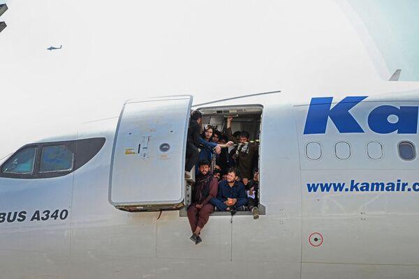Афганцы сидят в дверях самолета в аэропорту Кабула. - Sputnik Азербайджан