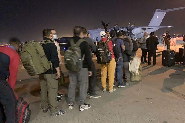 Французы и их коллеги из Афганистана в ожидании посадки на военный самолет в аэропорту Кабула. - Sputnik Азербайджан