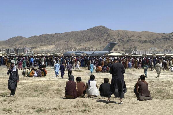 Сотни людей собрались возле транспортного самолета C-17 ВВС США по периметру международного аэропорта в Кабуле, Афганистан. - Sputnik Азербайджан