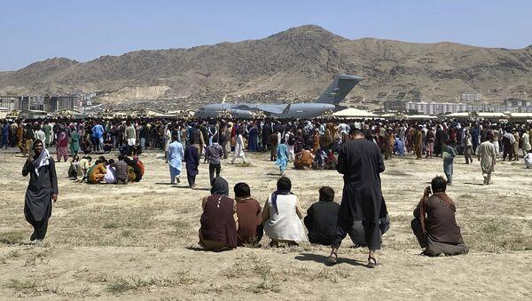 Сотни людей собрались возле транспортного самолета C-17 ВВС США по периметру международного аэропорта в Кабуле, Афганистан. - Sputnik Azərbaycan