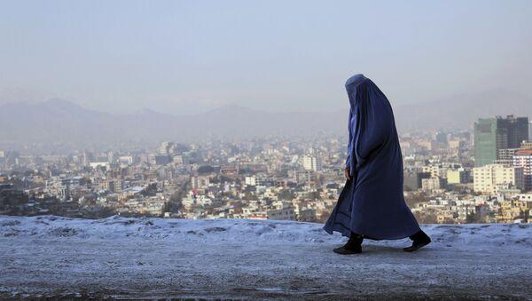 Женщина идет по улице с видом на город Кабул - Sputnik Азербайджан