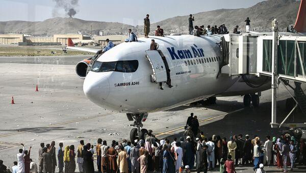 Афганцы забираются на самолет в аэропорту после вступления талибов в Кабул - Sputnik Азербайджан