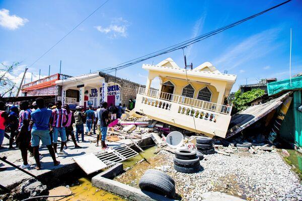 Le-Ke şəhərində 7,2 bal gücündə zəlzələ nəticəsində dağılmış evin yanında dayanan insanlar, Haiti. - Sputnik Azərbaycan