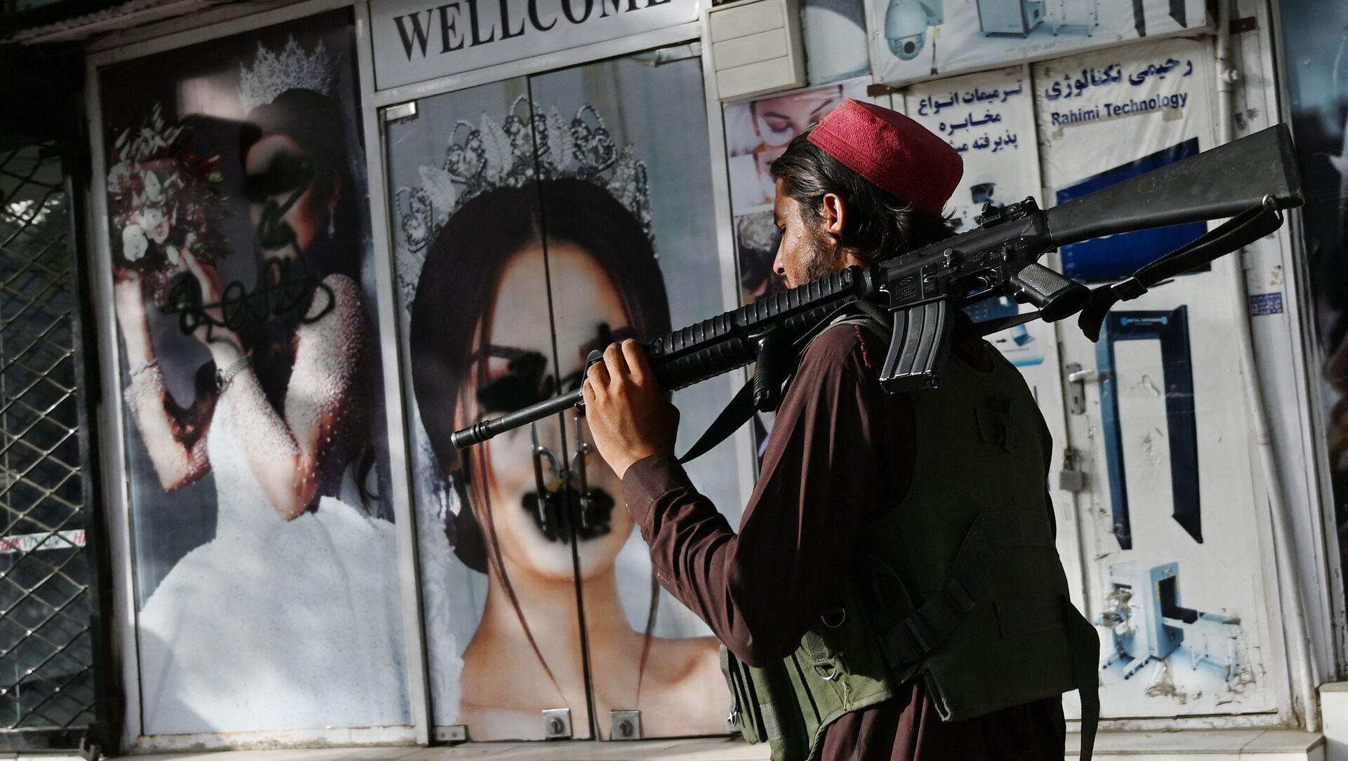 Боевик Талибана* у салона красоты с изображениями женщин, испачканных аэрозольной краской, в Шахр-э Нау в Кабуле - Sputnik Азербайджан, 1920, 22.08.2021