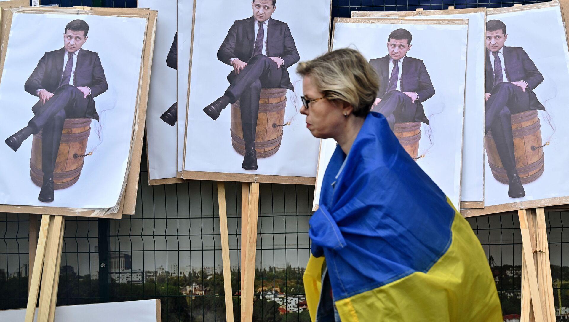 Женщина с флагом Украины проходит мимо плакатов с изображением Владимира Зеленского в Киеве, фото из архива - Sputnik Азербайджан, 1920, 21.08.2021