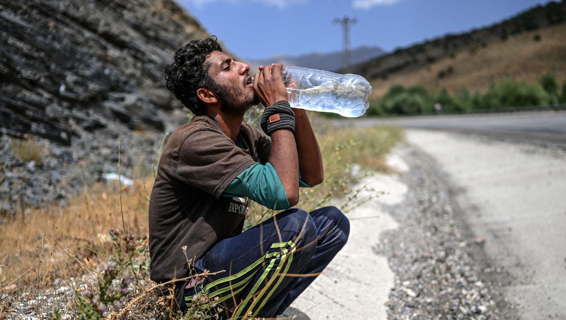 Афганский мигрант пьет воду в Татване - Sputnik Азербайджан, 1920, 23.08.2021