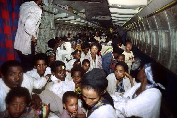 Эфиопские евреи сидят на самолете ВВС Израиля 25 мая 1991 года. За 36 часов было вывезено 14 325 человек  в рамках операции «Соломон». Всего было задействовано 24 транспортных самолёта типа C-130 израильских ВВС и 10 пассажирских самолётов авиакомпании El Al. - Sputnik Азербайджан