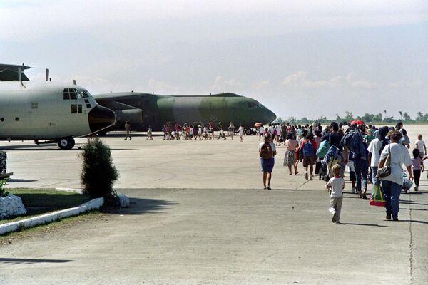 Американские военные выстроились в очередь, чтобы сесть на борт самолета, направляющегося в США, 22 июня 1991 года после эвакуации с американской авиабазы Кларк и военно-морской базы Субик, разрушенных извержением вулкана Пинатубо. - Sputnik Азербайджан