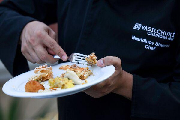 Посетитель дегустирует блюда на Неделе узбекской кухни в Азербайджане. - Sputnik Азербайджан