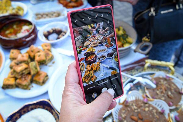 Посетитель фотографирует блюда на Неделе узбекской кухни в Азербайджане. - Sputnik Азербайджан