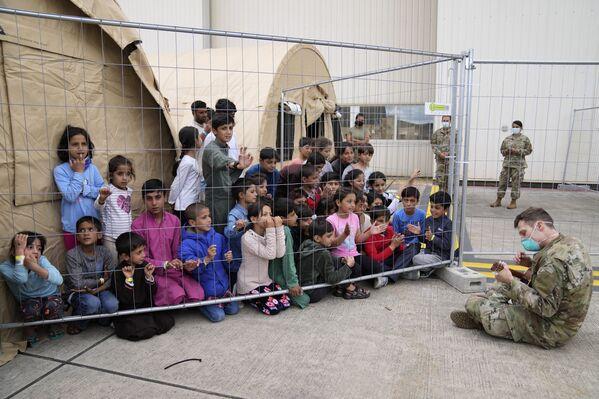 Американский солдат играет на гитаре для недавно эвакуированных афганских детей на авиабазе Рамштайн, Германия. - Sputnik Азербайджан