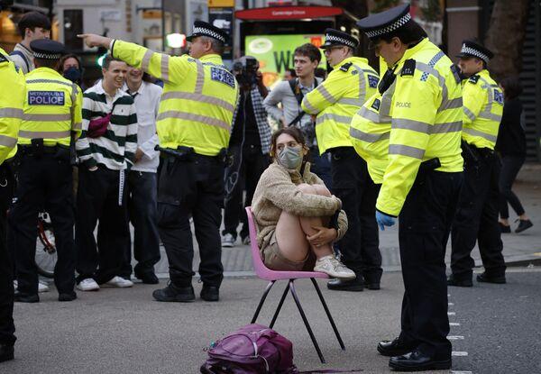 Офицер полиции разговаривает с климатическим активистом в центре Лондона. - Sputnik Азербайджан