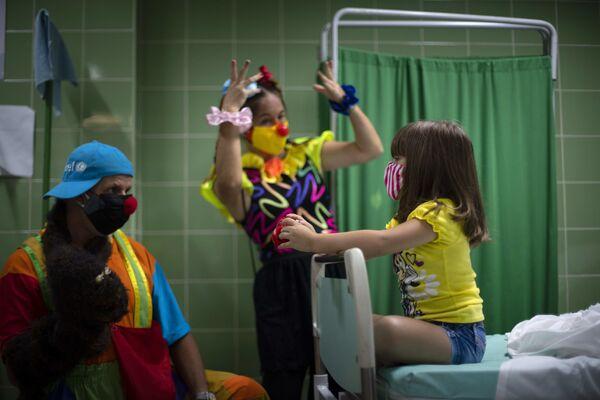 Клоуны развлекают вакцинировавшуюся пациентку в одной из больниц Гаваны, Куба. - Sputnik Азербайджан