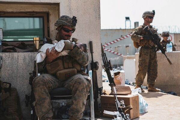 Морской пехотинец США с ребенком на руках во время эвакуации в международном аэропорту Кабула, Афганистан. - Sputnik Азербайджан