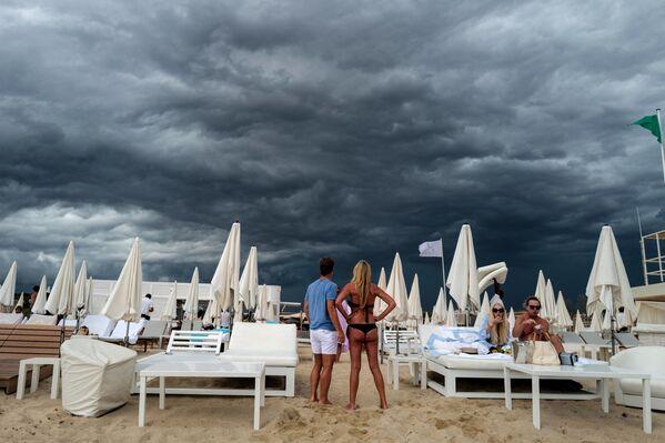 Люди смотрят на темные облака на пляже в Раматюэле, недалеко от Сен-Тропе, на юге Франции. - Sputnik Азербайджан