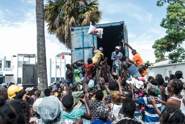 Мужчина бросает мешок с рисом в толпу в время раздачи еды и воды пострадавшим от землетрясения в Ле-Ке, Гаити. - Sputnik Азербайджан