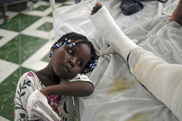 Юнаика в больнице рядом со своей матерью, пострадавшей в результате землетрясения  Ле-Ке, Гаити. - Sputnik Азербайджан