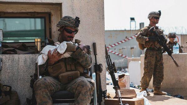 Морской пехотинец США с ребенком на руках во время эвакуации в международном аэропорту Кабула, Афганистан - Sputnik Azərbaycan