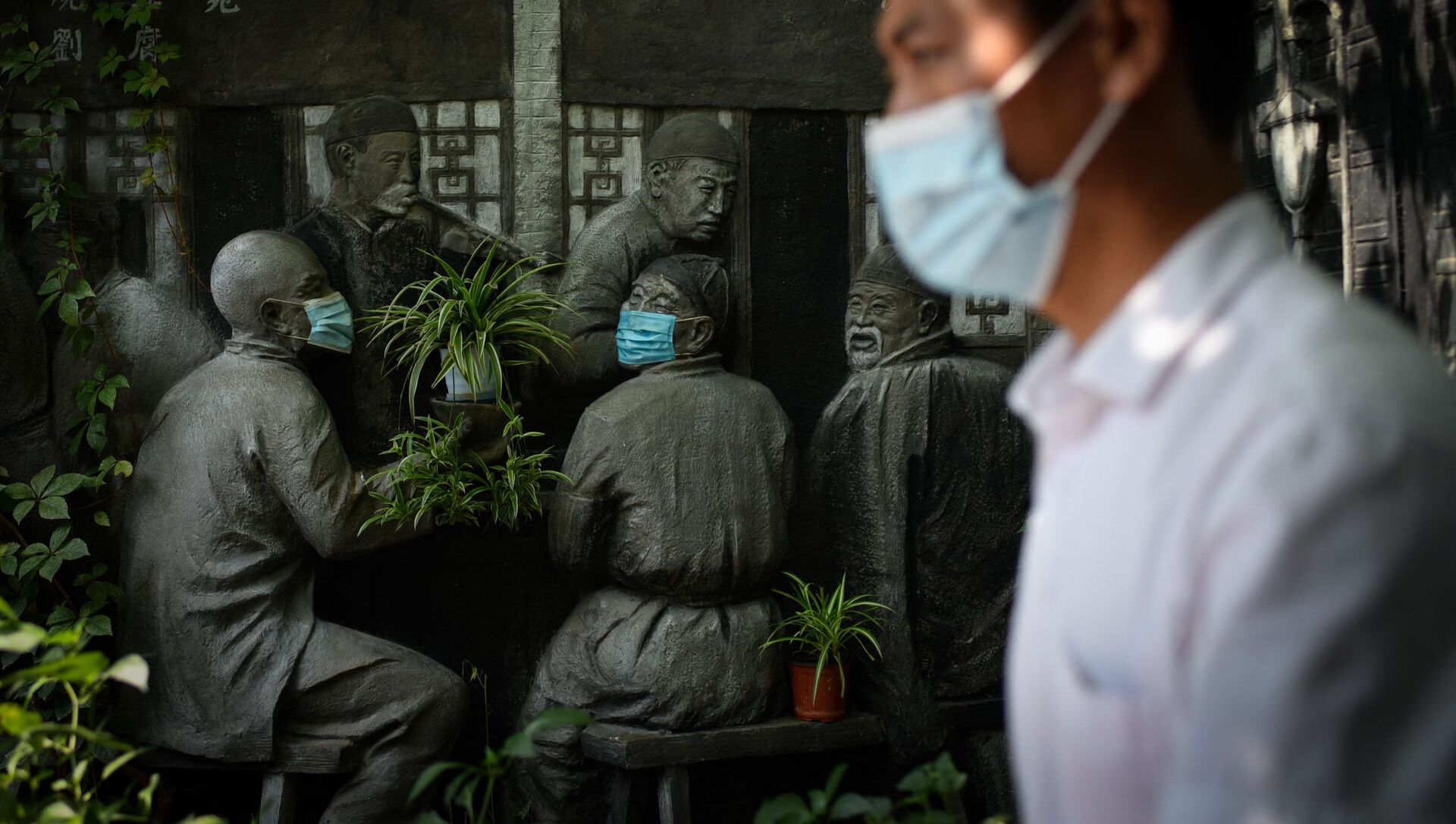 Мужчина проходит мимо скульптур в масках возле ресторана в Пекине - Sputnik Azərbaycan, 1920, 12.09.2021