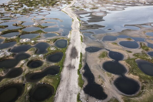 Seneqalda yağış mövsümü zamanı su basmış duz mədənlərindən keçən bir yolun havadan görüntüsü. - Sputnik Azərbaycan