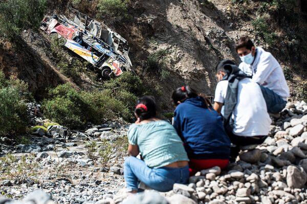 İnsanlar Peruda avtobusun qəzaya uğradığı yerin yaxınlığında oturublar. - Sputnik Azərbaycan
