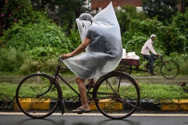 Hindistanda Faridabadda leysan zamanı plastik torba ilə örtülmüş velosipedçi. - Sputnik Azərbaycan
