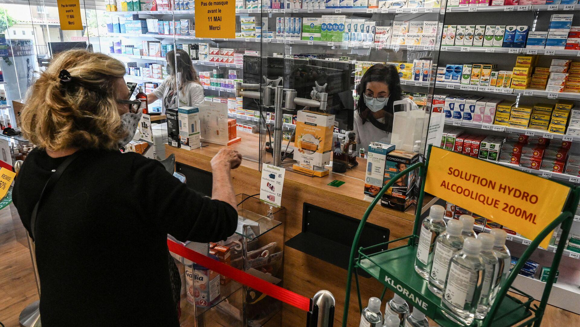Женщина покупает лекарства в аптеке в Пероле, южная Франция - Sputnik Азербайджан, 1920, 17.09.2021