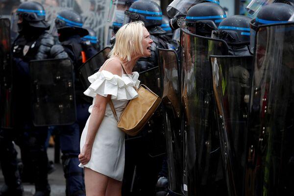 Женщина противостоит сотрудникам полиции во время демонстрации против ограничений в Париже. - Sputnik Азербайджан