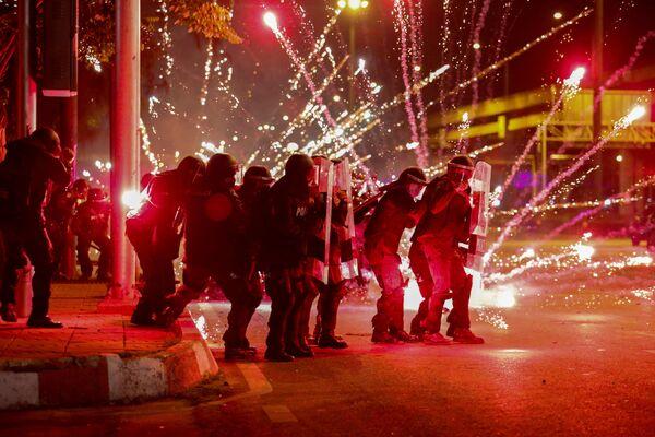 Протестующие забрасывают петардами полицию на антиправительственной акции протеста в Бангкоке, Таиланд. - Sputnik Азербайджан